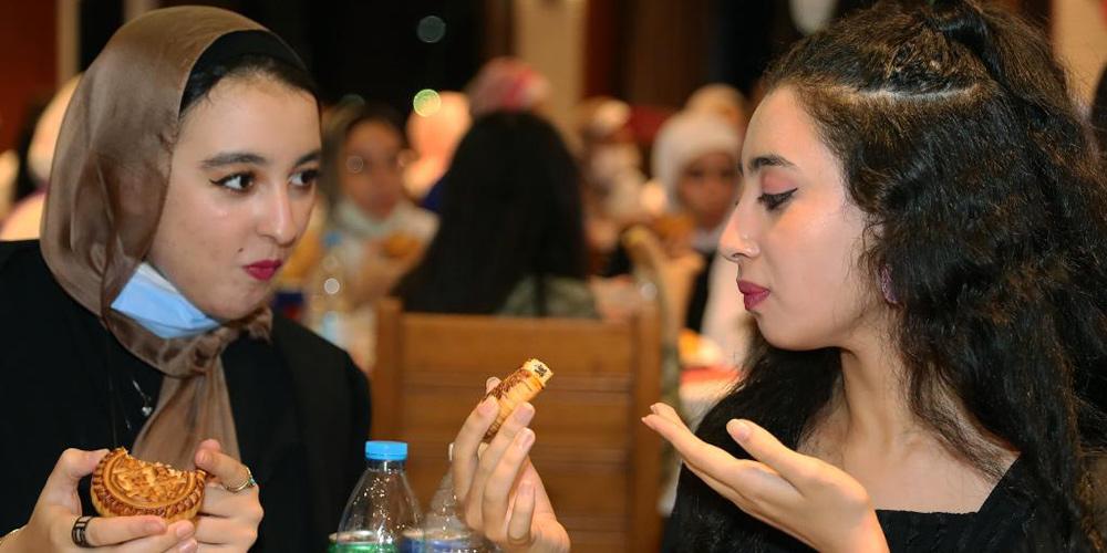 Estudantes egípcios apreciam bolos lunares para celebrar o Festival do Meio Outono da China